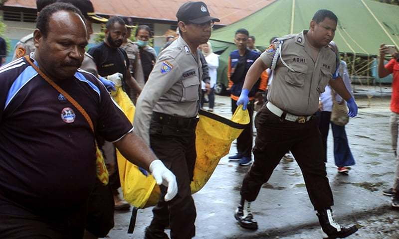 Indonesian police carry the body of a flood victim in Sentani, Papua Province, Indonesia. ─ AP