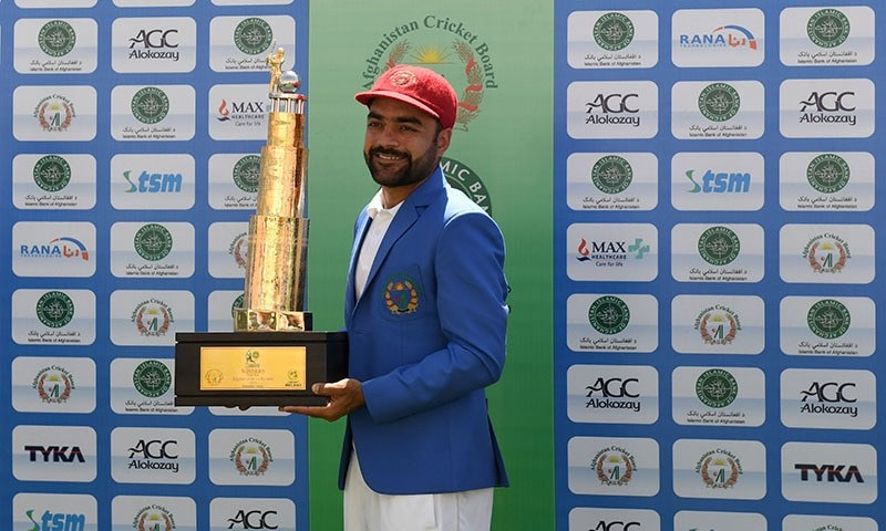 Afghanistan's Rashid Khan poses with the trophy after winning the Test match between Afghanistan and Ireland at the Rajiv Gandhi International Cricket Stadium in the northern Indian city of Dehradun on March 18, 2019. — AFP