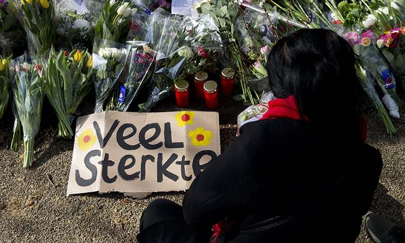"A sign reads ""Lots of Strength"" as a mourner lays flowers at a makeshift memorial for victims of a shooting incident in a tram in Utrecht, Netherlands on Tuesday, March 19, 2019. — AP"