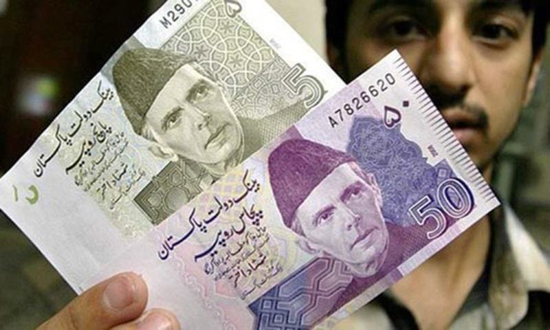 A man holds up various notes of Pakistani currency. — File