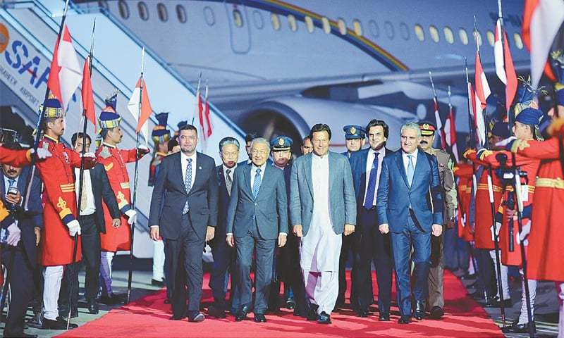 Rawalpindi: Prime Minister Imran Khan receives Prime Minister of Malaysia Mahathir Mohamad upon his arrival at Nur Khan airbase on Thursday.—APP