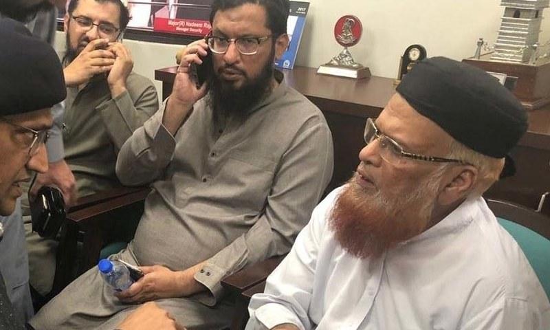 DIG East Amir Farooq speaks to Mufti Taqi Usmani after the latter escaped an assassination attempt near Shahrah-i-Faisal. — DawnNewsTV