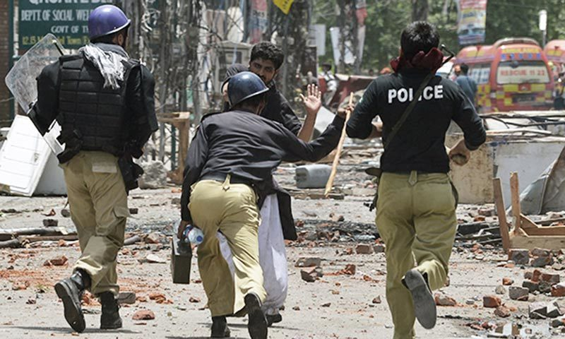 Policemen clashing with Pakistan Awami Tehreek (PAT) workers in the 2014 Model Town incident. — File