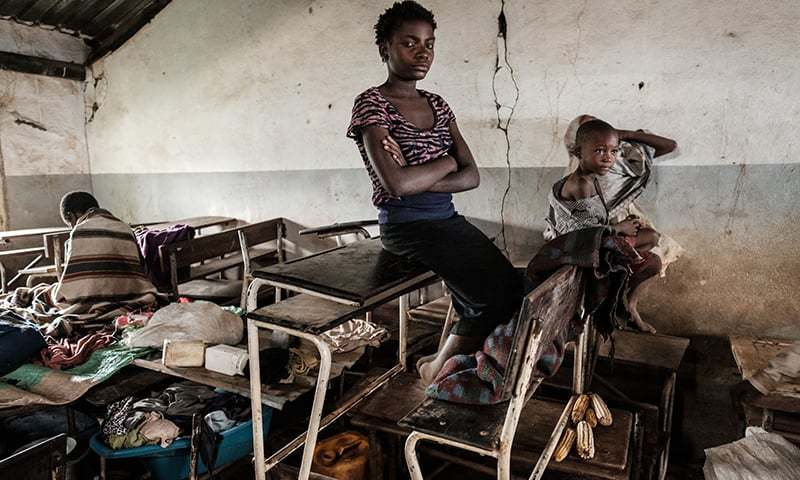 Juma Luis Elia (C), 13, sits on a school desk where she sleeps at a local school where she took shelter in Buzi, Mozambique, after the area was hit by the Cyclone Idai. ─ AFP