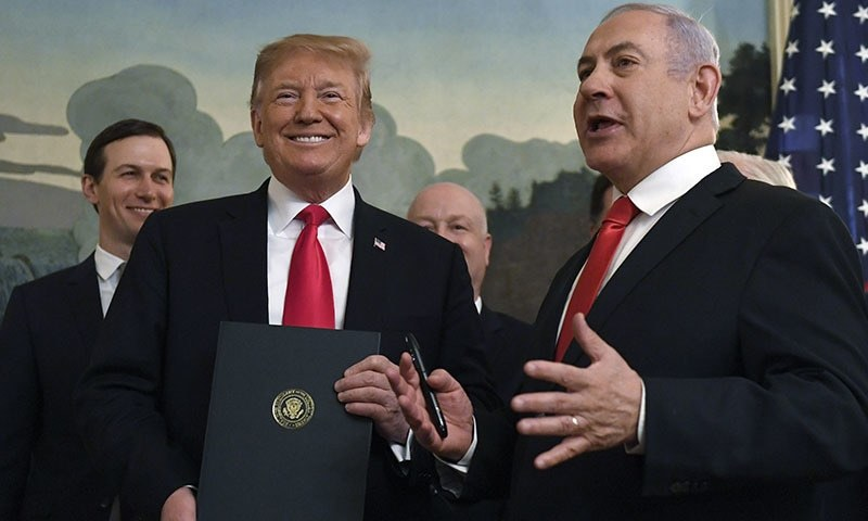 President Donald Trump smiles as he holds a proclamation as Israeli Prime Minister Benjamin Netanyahu, right, speaks in the Diplomatic Reception Room at the White House in Washington on Monday, March 25, 2019. — AP