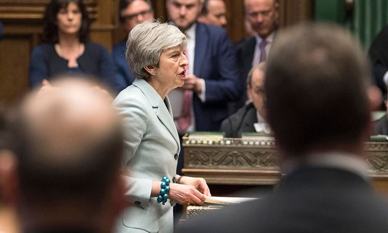 A handout photograph released by the UK Parliament shows Britain's Prime Minister Theresa May making a statement in the House of Commons in London on March 25, 2019 outlining the next steps that parliament will take in the Brexit process. ─ AFP