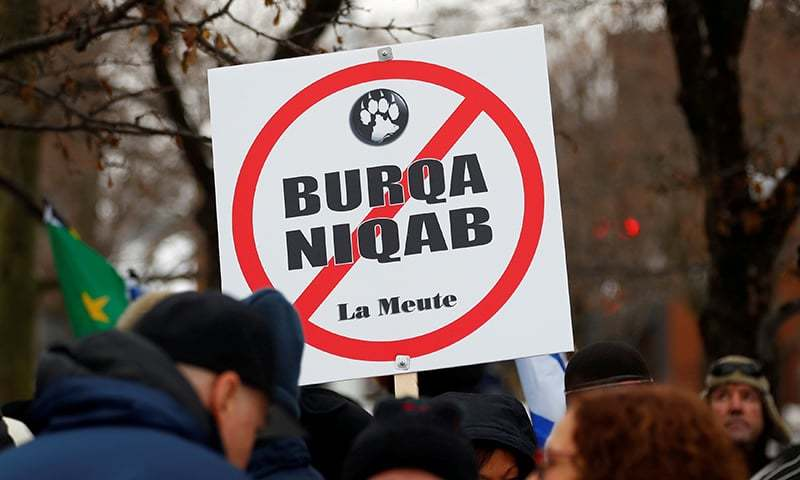 A sign opposing religious attire is displayed during protests by groups La Meute and Storm Alliance in Quebec City, November 25, 2017. — Reuters