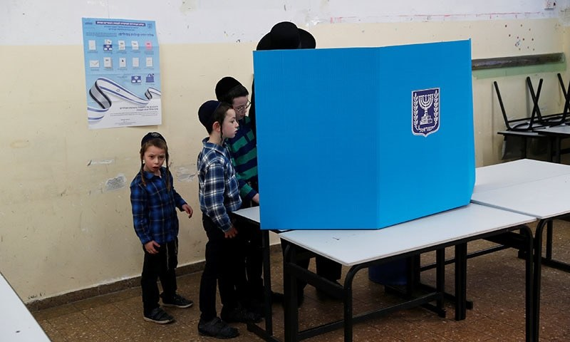 Ultra-Orthodox Jewish boys stands next to their father behind a voting booth as Israelis vote in a parliamentary election, at a polling station in Jerusalem on April 9, 2019. — Reuters