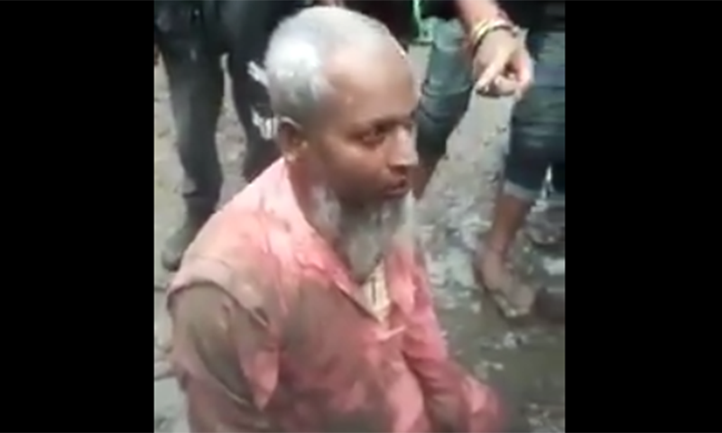 A screengrab from a video circulating on social media shows Shaukat Ali, thrust into mud and being assaulted by a mob in Assam. — Source: Twitter