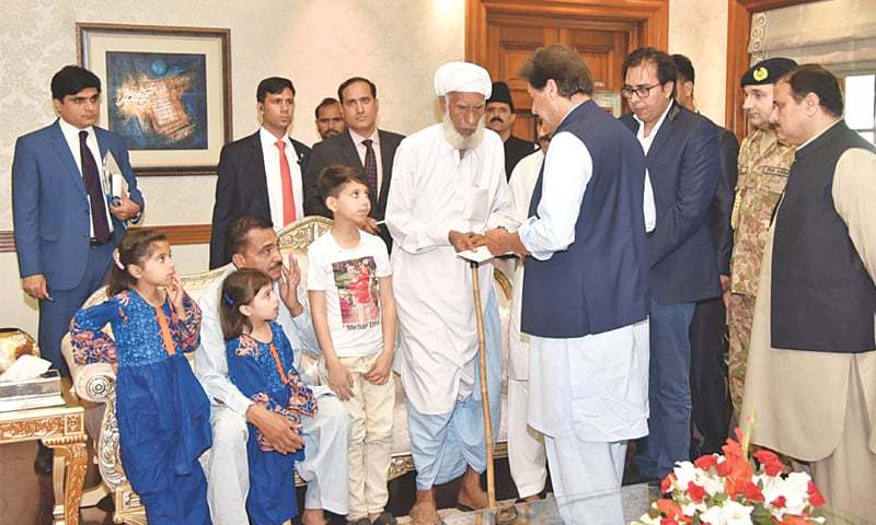 Prime Minister Imran Khan distributes cheques among family members of the Sahiwal incident on Wednesday. —APP