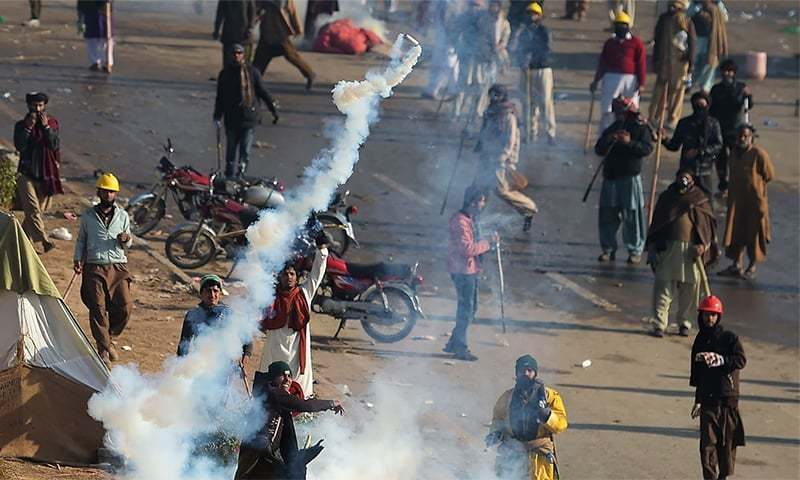A TLP protesters throws a tear gas shell back towards police during a clash in Islamabad on Nov 25, 2017. ─ AFP/File