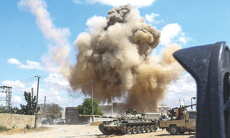 A smoke plume rises after an air strike behind a tank and pickup trucks mounted with turrets belonging to forces loyal to Libya's internationally-recognised government during clashes 30 kilometres south of the capital Tripoli. — AFP