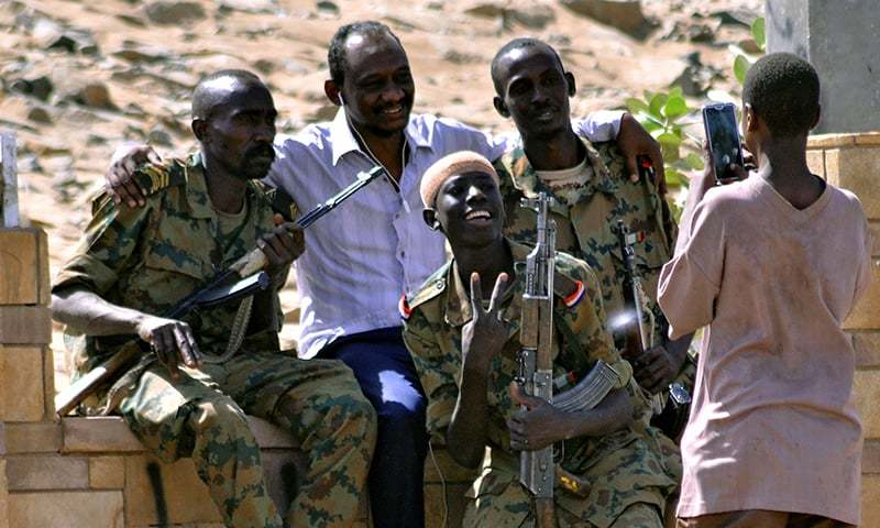 Sudanese military officers and a demonstrator pose for a photograph in celebration after Defence Minister Awad Ibn Auf stepped down as head of the country's transitional ruling military council, as protesters demanded quicker political change, near the Defence Ministry in Khartoum. ─ Reuters