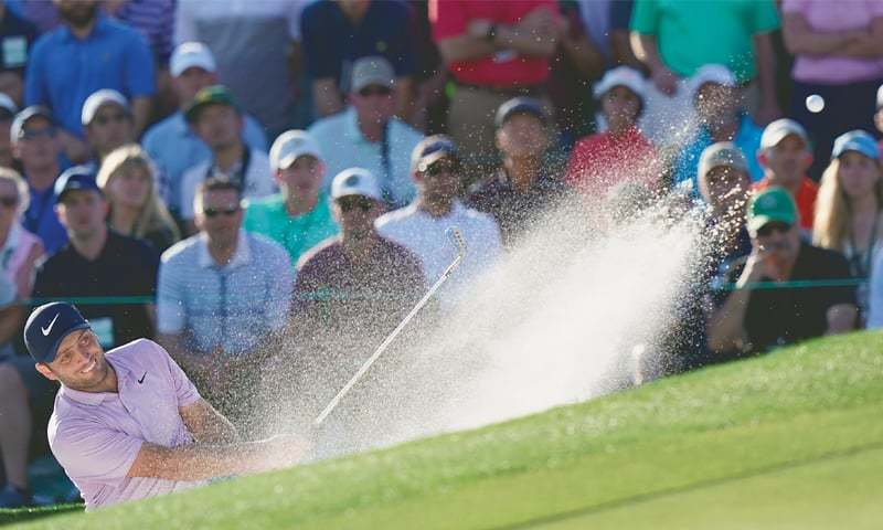 AUGUSTA: Francesco Molinari of Italy hits from a bunker on the 18th hole during the third round of the Masters.—AP