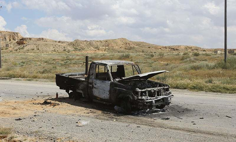 A charred vehicle sits on a road west of the city of Aziziah, some 60 kilometres southwest of the capital Tripoli, on April 14, 2019. — AFP