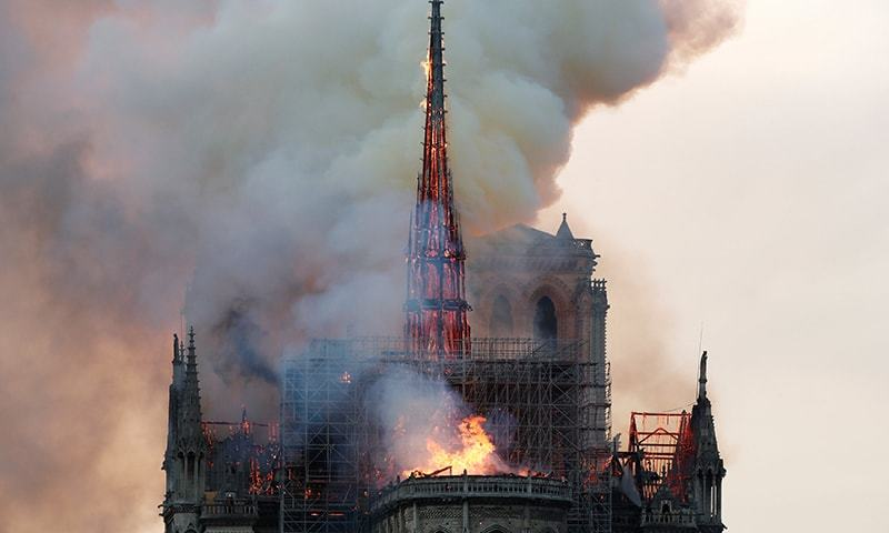 Smoke billows as fire engulfs the spire of Notre Dame Cathedral in Paris. ─ Reuters