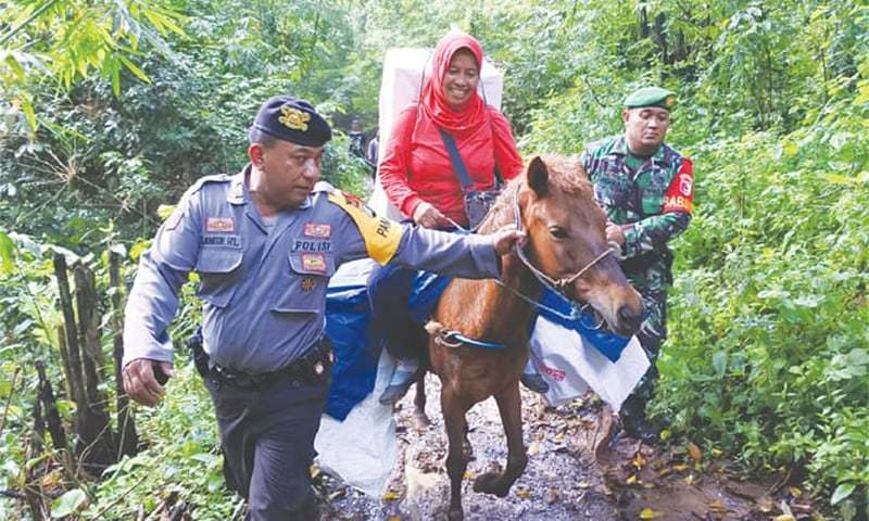 Indonesian army and police guard ballot boxes and election material during their distribution on horseback to Meru Betiri National Park in Jember area of East Java province on Monday.—Reuters