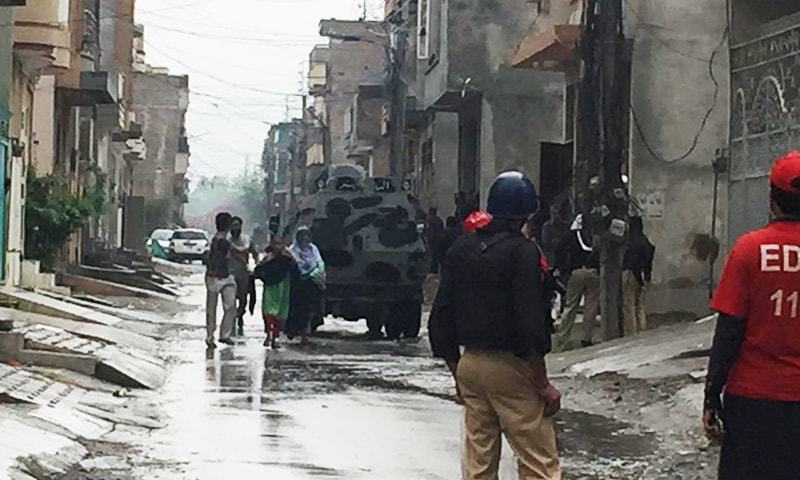 Police and rescuers help a family evacuate the operation site. — Arif Hayat