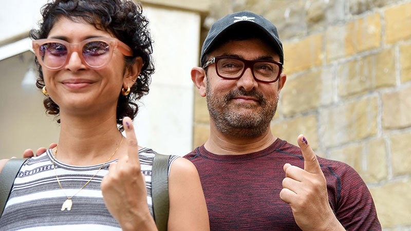 Bollywood actor Aamir Khan along with his wife and film director Kiran Rao pose for photographs after casting their vote at a polling station in Mumbai on April 29, 2019. — AFP
