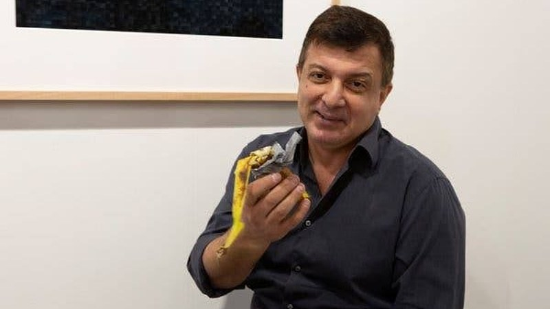 David Datuna, who describes himself as a Georgian-born American artist living in New York, walks up to the banana and pulls it off the wall with the duct tape attached.