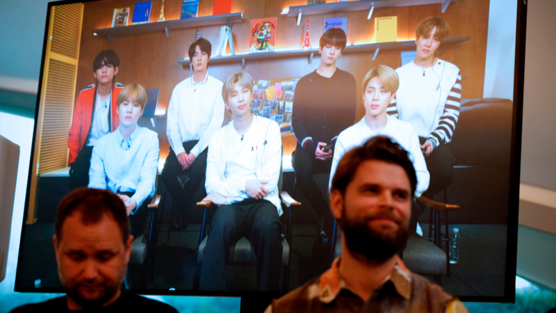 Danish artist Jakob Kudsk Steenson (right) sits in front of a monitor live-streaming the South Korean boyband BTS, during the announcement of his new work Catharsis, at the launch of the global public art project Connect, BTS in London on Jan 14, 2020.—AFP