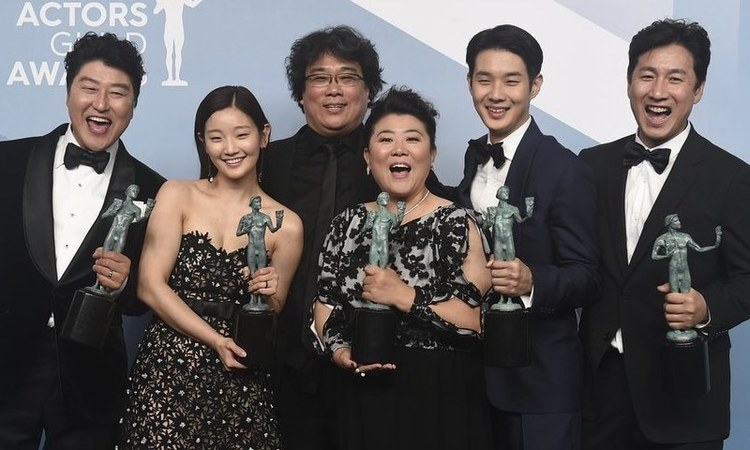 """Kang-Ho Song, from left, Park So-dam, Bong Joon-ho, Jang Hye-jin, Choi Woo-shik, and Lee Sun Gyun pose in the press room with the award for outstanding performance by a cast in a motion picture for """"Parasite"""" at the 26th annual Screen Actors Guild Awards —Jordan Strauss/Invision/AP"""
