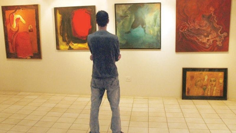 An art connoisseur appreciates different pieces during more 'normal' times in this file photo.—White Star