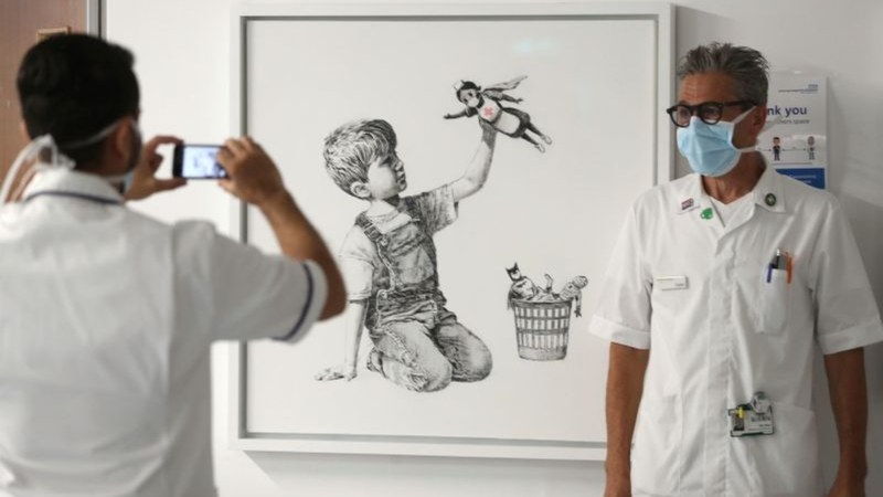A member of staff has their photograph taken in front of new artwork painted by Banksy on display to staff and patients at a hospital in Southampton, England on May 7, 2020. Andrew Matthews—PA /AP