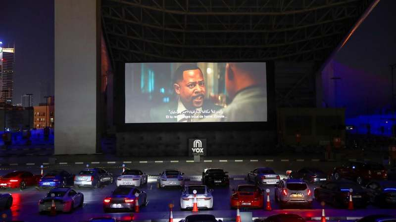 People sit in their cars watching a movie in a drive-in cinema at the Mall of the Emirates, following the outbreak of the coronavirus disease (COVID-19), in Dubai, United Arab Emirates, May 13, 2020. REUTERS/Ahmed Jadallah