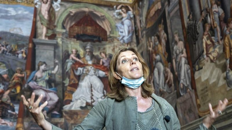 Vatican Museums director Barbara Jatta speaks to the media as she stands in front of Raphael's oil painted feminine figure known as 'Allegory of Justice', left, in the Constantine Hall at the Vatican Museums, Wednesday, May 3, 2020. The Vatican Museums announced last month that after restorations they have determined that two of the female figures in the Hall of Constantine were painted in oil by Raphael himself and not by his workshop. (AP Photo/Domenico Stinellis)