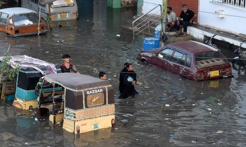 People wade through a flooded street after heavy monsoon rains in Karachi on July 27. — AFP/File