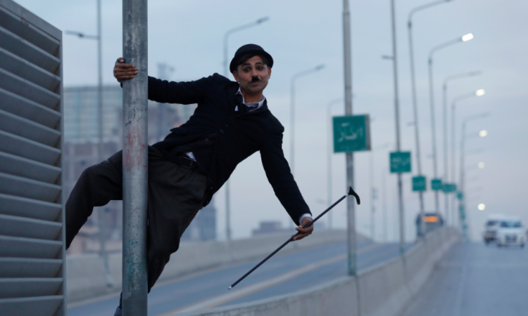 Usman Khan, 29, dressed up as Charlie Chaplin, performs along the street in Peshawar. — All photos by Reuters