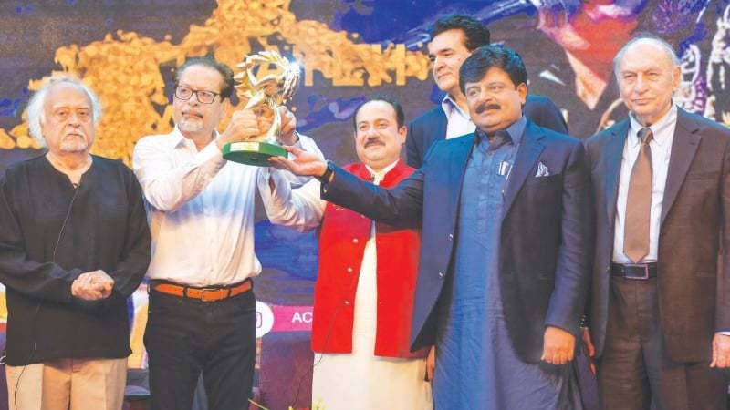 Ustad Rahat Fateh Ali Khan (in red vest) receives his award on Tuesday. —Fahim Siddiqi/White Star