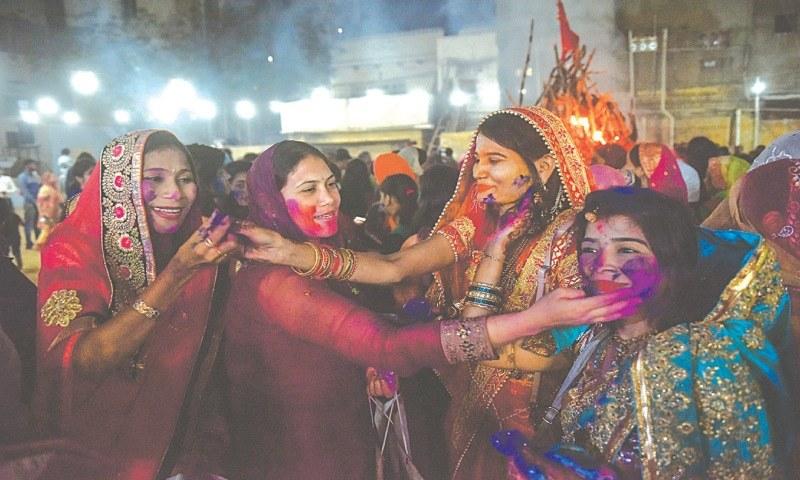 کراچی میں ہولی مناتی ہوئی خواتین ایک دوسرے کو رنگ لگا رہی ہیں