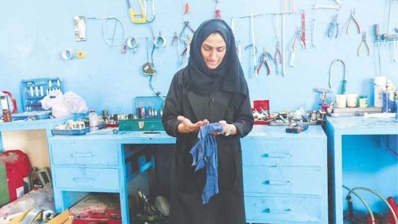 Huda al Matrooshi cleans her hands at her garage in Sharjah.—Reuters