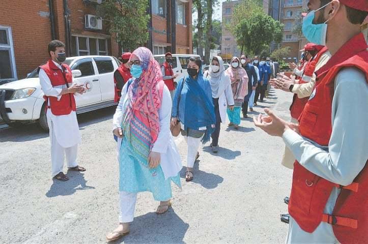 ریڈ کراس کی بین الاقوامی کمیٹی کے ممبران پشاور کے لیڈی ریڈنگ ہسپتال کے ڈاکٹروں اور دیگر عملے کو تالیاں بجا کر داد دے رہے ہیں— شہباز بٹ/ وائٹ اسٹار