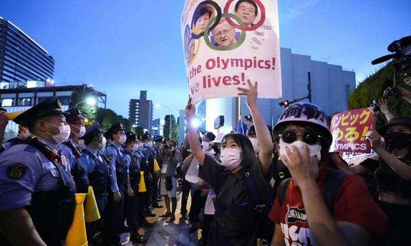 ٹوکیو میں نیشنل اسٹیڈیم کے باہر مظاہرین موجود ہیں—فوٹو: اے پی