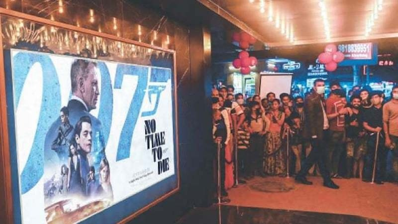Spectators stand beside a poster of No Time to Die at a cinema in New Delhi on Thursday.—AFP