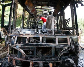 Rescue workers and security officials collect evidence from the burnt bus. –Photo by Reuters.