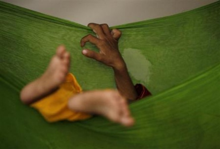 A child sleeps in a hammock at a camp for internally displaced persons — Reuters