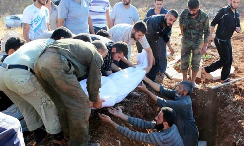 A handout picture released by the Syrian opposition's Shaam News Network on July 15, 2012 shows Syrian mourners burying a body of a man in Baba Amr in the flashpoint city of Homs. -Photo by AFP