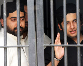 Shahrukh Jatoi (R) gestures while his accomplice Siraj Talpur looks on from a court lockup. -Photo by AFP