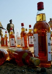 August 2013: Police in Faisalabad stand over confiscated bottles of toxic whiskey that was brewed by illegal brewers and killed over 15 men. Such brewers mostly use empty bottles of established whiskey brands.