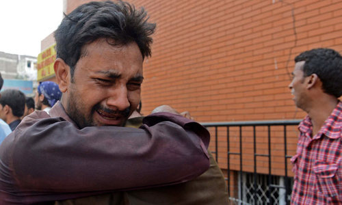 A Christian mourns the killing of his relative, in two suicide bomb attacks on a church in Peshawar. — File photo