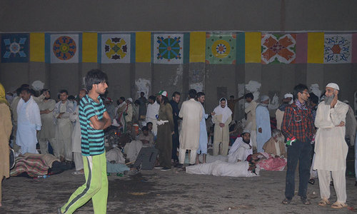 The image shows PAT supporters taking shelter under the bridge at Zero Point. — Photo by Irfan Haider