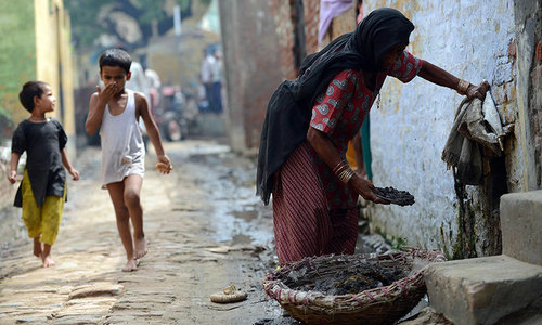 60 year old Indian manual scavenger Kela collects human waste while cleaning a toilet in Nekpur village, Muradnagar in Uttar Pradesh, some 40kms east of New Delhi. — Photo by AFP