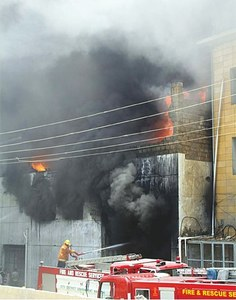 Raging fire hinders rescue efforts as factory workers help themselves