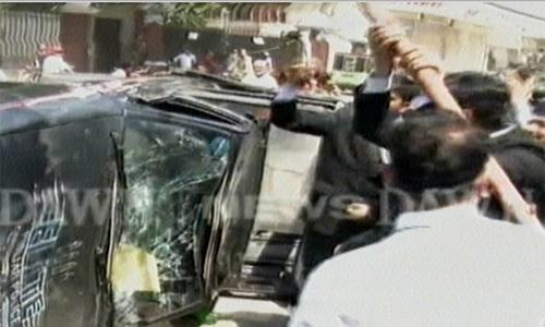 An Elite Forces vehicle being vandalised by protesters. ─ DawnNews screengrab