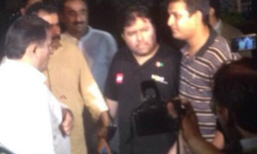 Shoaib Ahmad Shaikh talking to FIA director Shahid Hayat as reporters look on