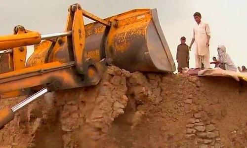 A bulldozer demolishing a house in the I/11 slum. ─ DawnNews screengrab